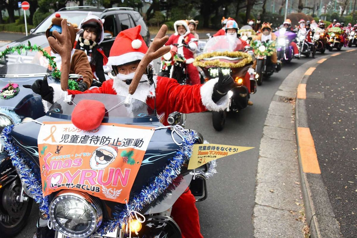 Motorcyclists dressed in Santa Claus and reindeer outfits ride down the streets in downtown Tokyo on Dec 23, 2015.