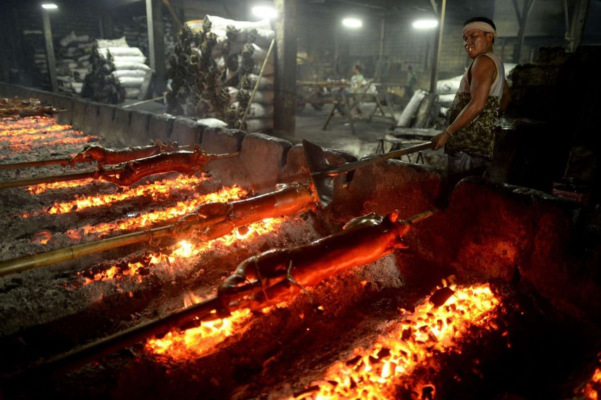 A worker arranges coals to roast bamboo skewered pigs, a regular fare at festivities in the Philippines, in Manila on Dec 23, 2015.