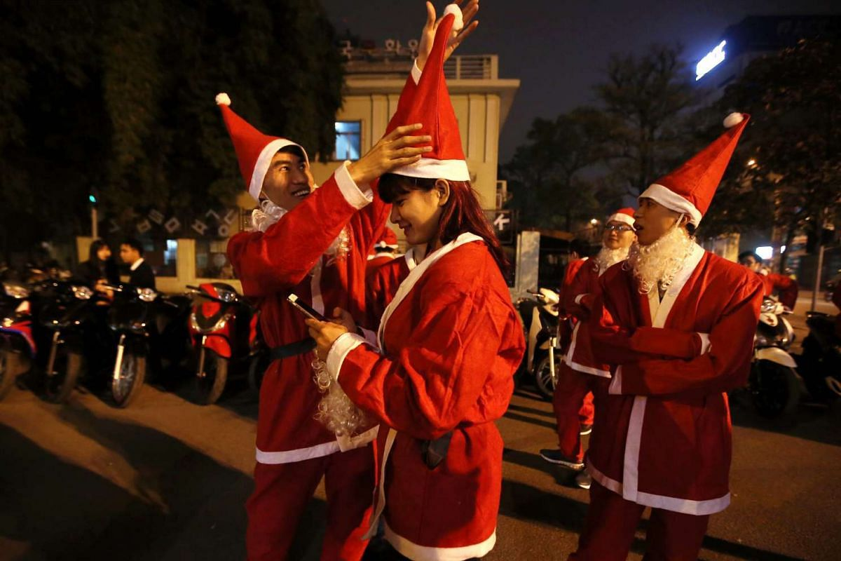 Vietnamese teenagers wearing Santa Claus costumes gather in a street in preparation to deliver presents to children in Hanoi on Dec 23, 2015.
