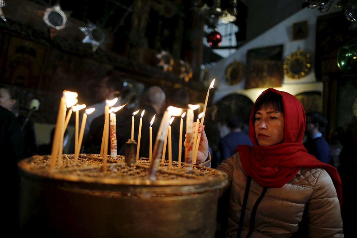 A woman lights a candle in the Church of the Nativity, the site revered by Christians as Jesus' birthplace, in the West Bank town of Bethlehem on Dec 23, 2015.