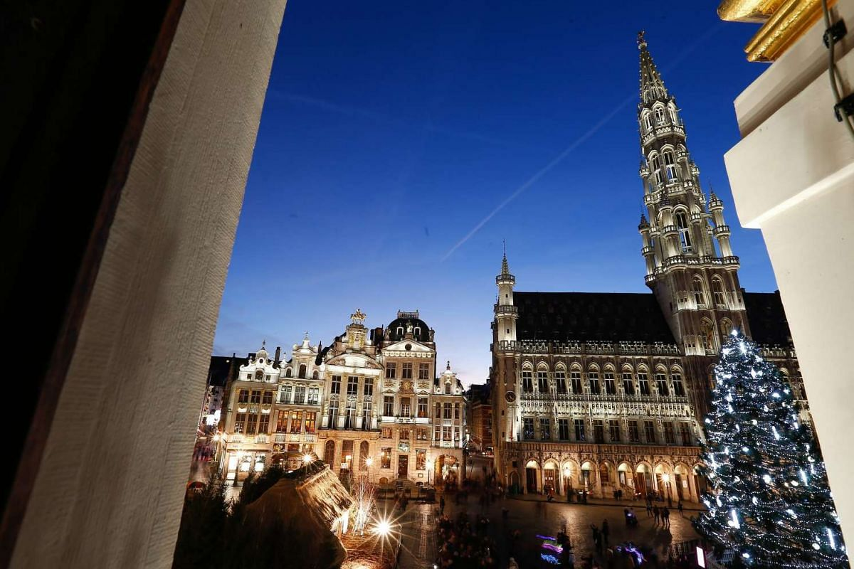 View of a Christmas tree and lights illuminating the Grand Place in Brussels, Belgium.