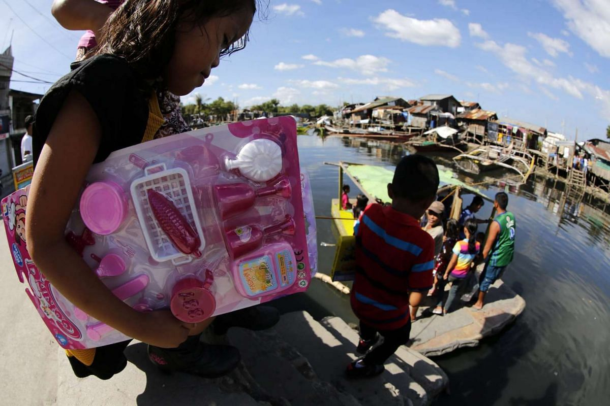 A Filipino girl holding a gift boards a makeshift raft on Christmas Day in Paranaque city, south of Manila, Philippines, Dec 25, 2015.