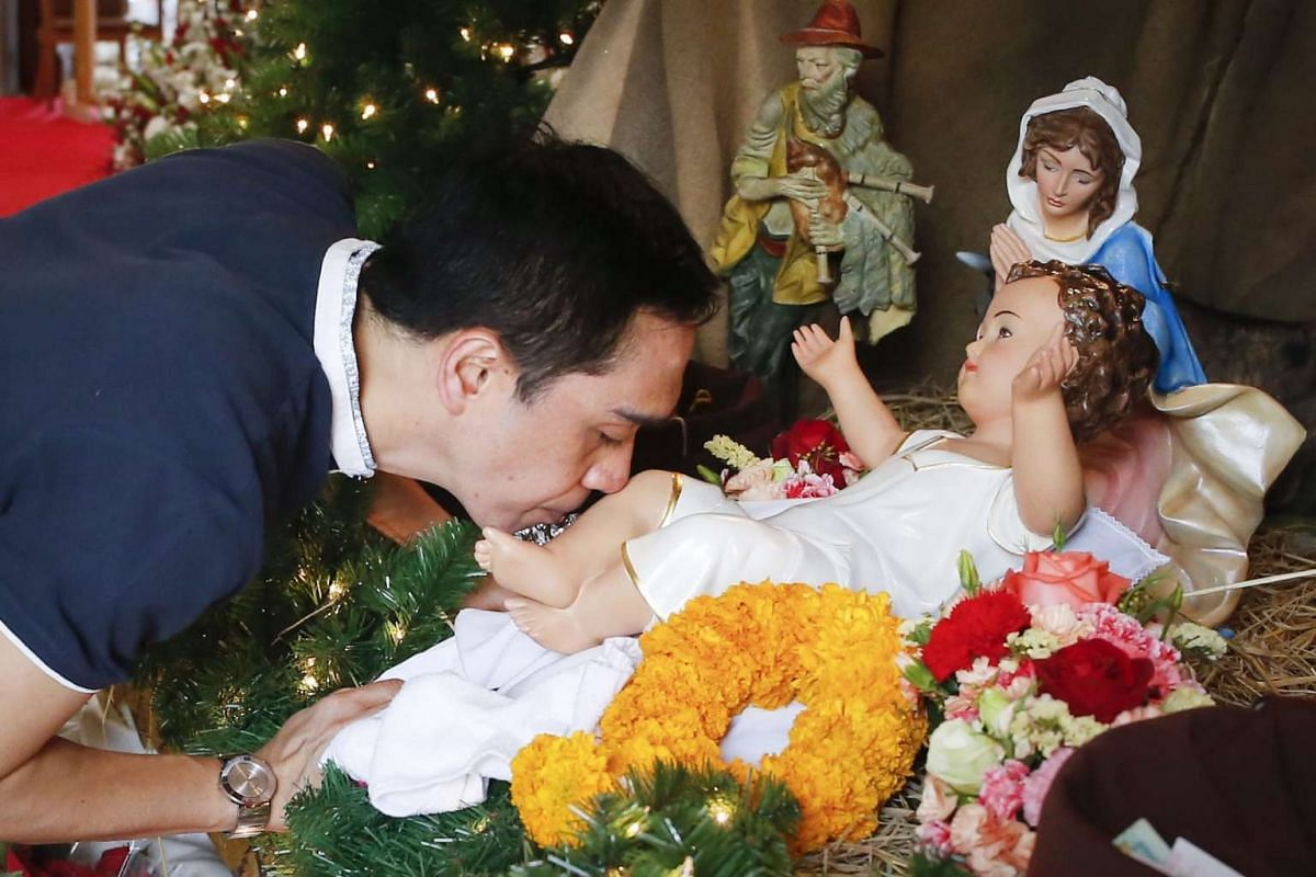 A Thai Christian kisses the baby Jesus doll part of a Nativity scene in a church during a morning Christmas day mass in Bangkok, Thailand, Dec 25, 2015.