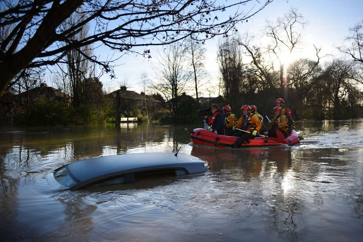 FLOODS IN ENGLAND: Members of the emergency services paddling down Huntington Road past a submerged car after the adjacent River Foss burst its banks in York, northern England, on Dec 27, 2015.