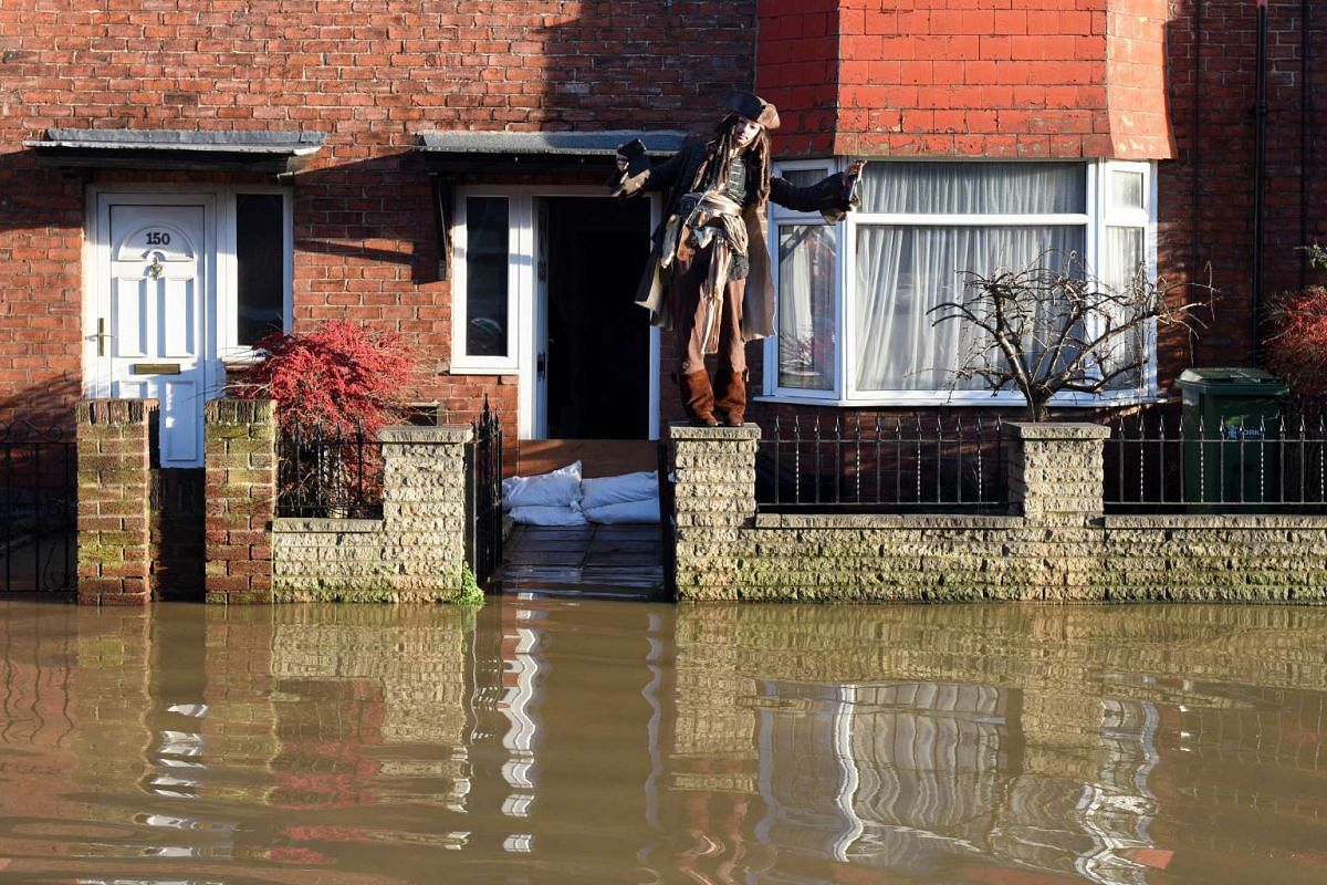 FLOODS IN ENGLAND: A resident, dressed as the character Captain Jack Sparrow from the Pirates Of The Caribbean films, standing outside his flooded house in York, northern England, on Dec 27, 2015.