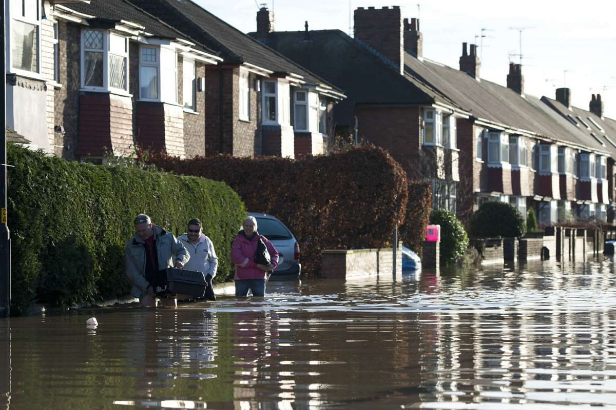 FLOODS IN ENGLAND: People wading through floodwaters on Huntington Road, adjacent to the River Foss which burst its banks in York, northern England, on Dec 27, 2015.