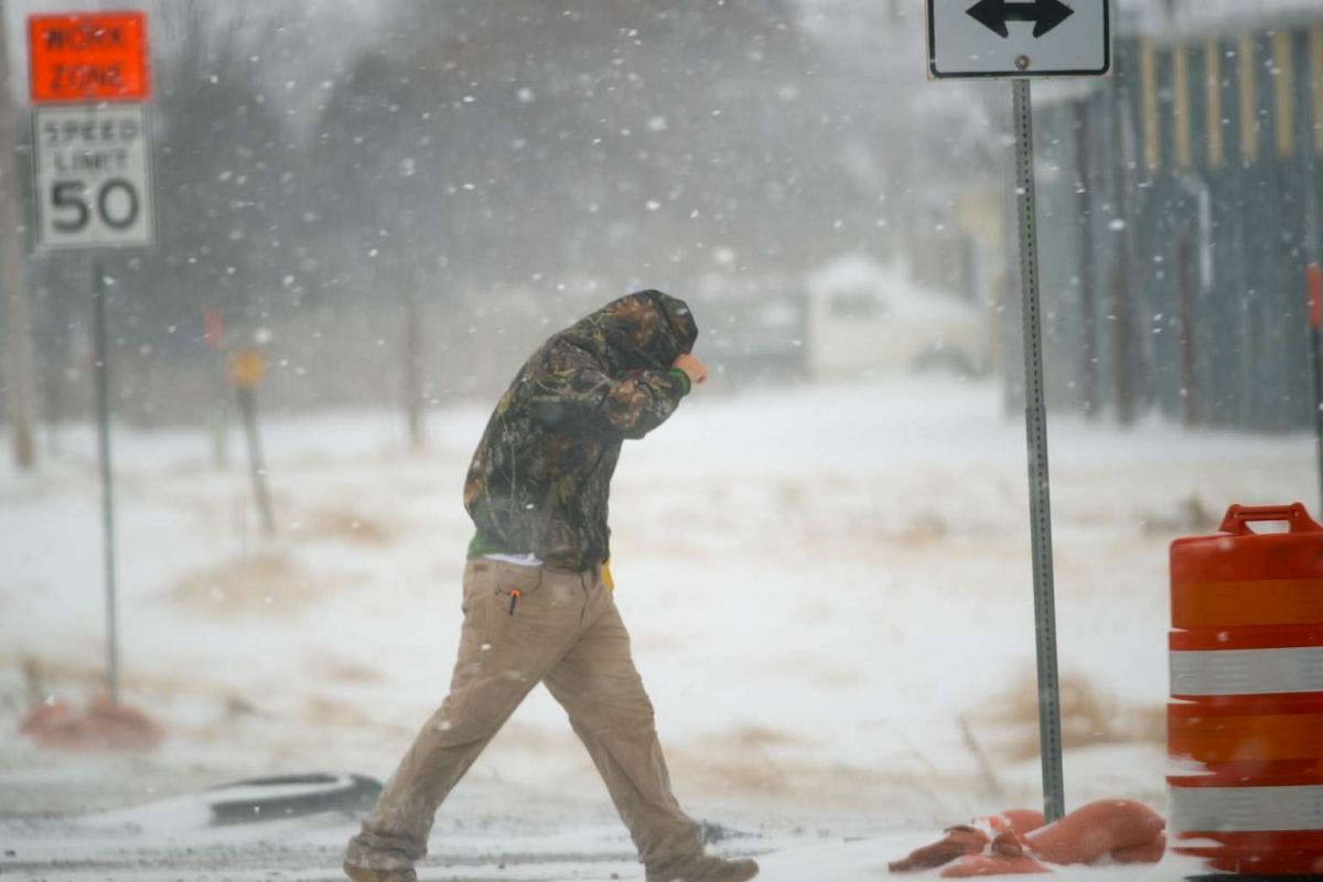 STORM IN US: A highway worker trying to shield himself while walking to his truck on Dec 27, 2015, in Lubbock, Texas.