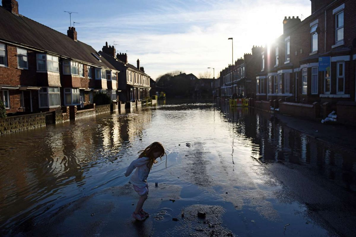A girl playing in floodwaters on a residential street adjacent to the River Foss which burst its banks in York, northern England on Dec 27, 2015.