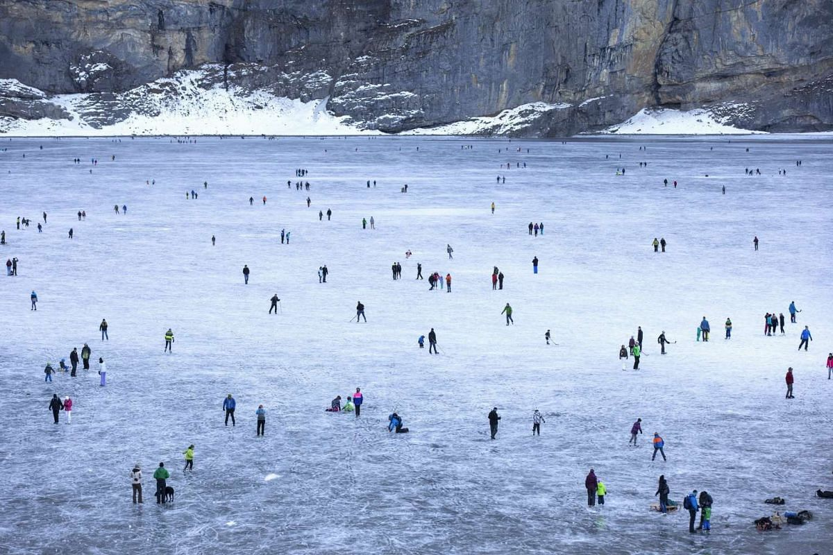 People skating and walking on the frozen Oeschinensee mountain lake near Kandersteg in the Bernese Oberland, Switzerland on Dec 25, 2015.