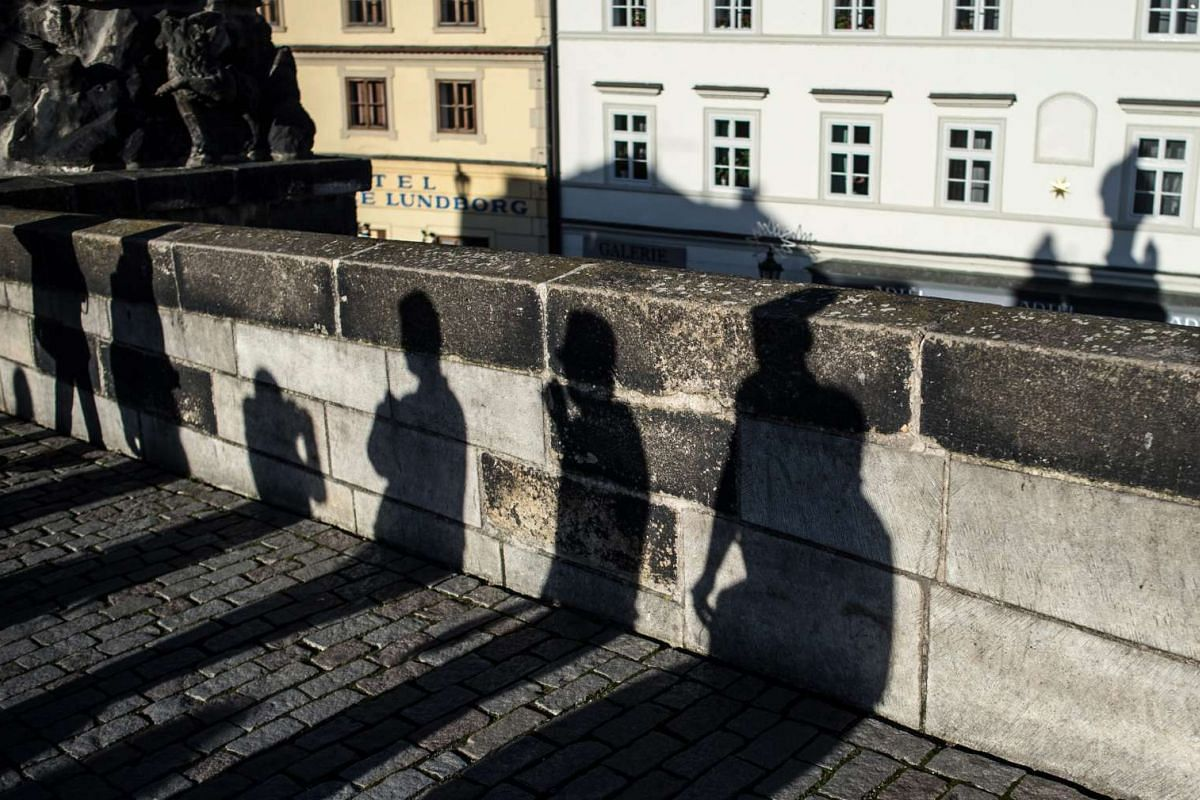 Shadows of people crossing the mediaeval Charles Bridge on a warm day in Prague, Czech Republic on Dec 26, 2015.
