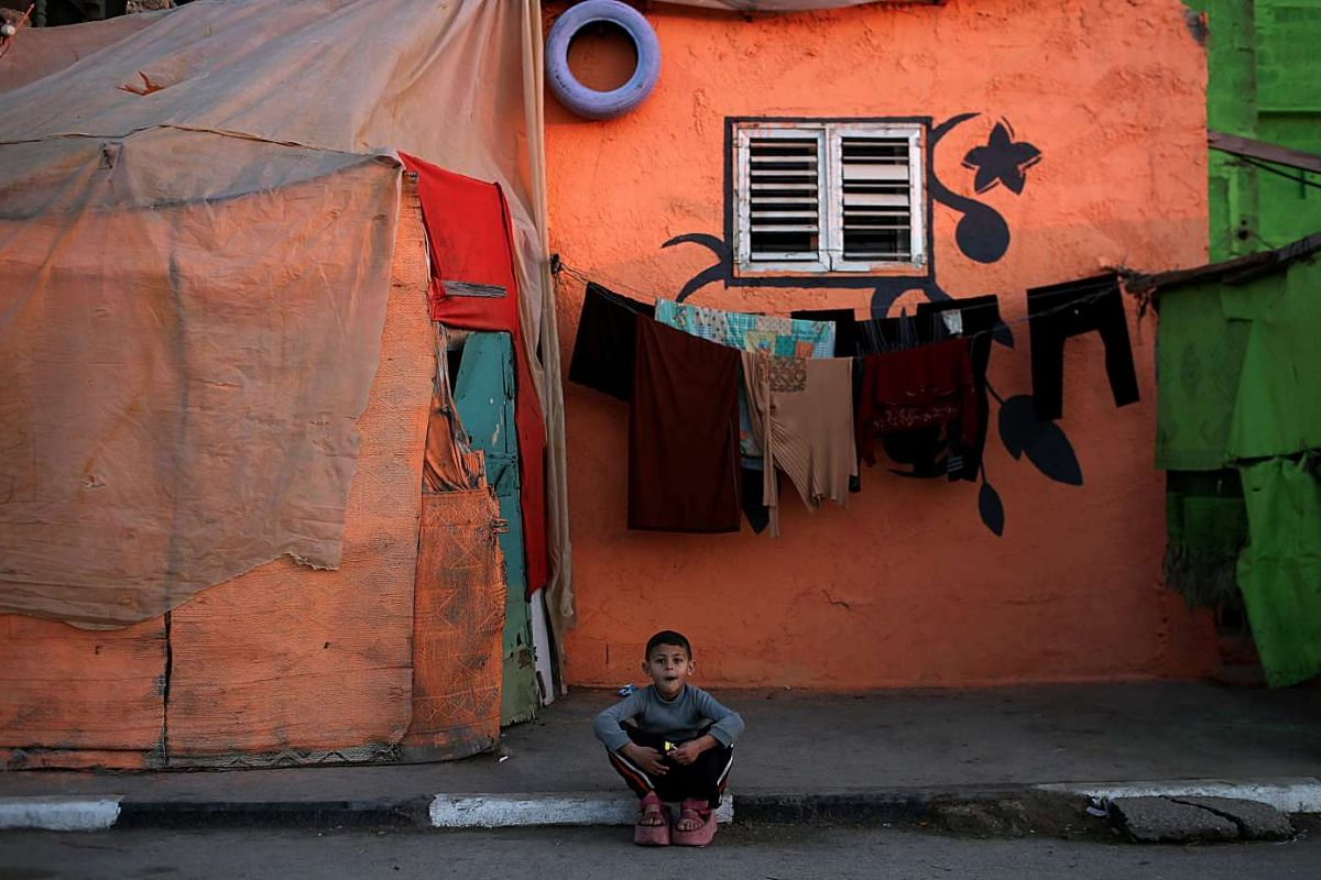 A Palestinian boy sitting outside his house, which was painted by Palestinian artists, in Al Shataa refugee camp in Gaza City on Dec 26, 2015.