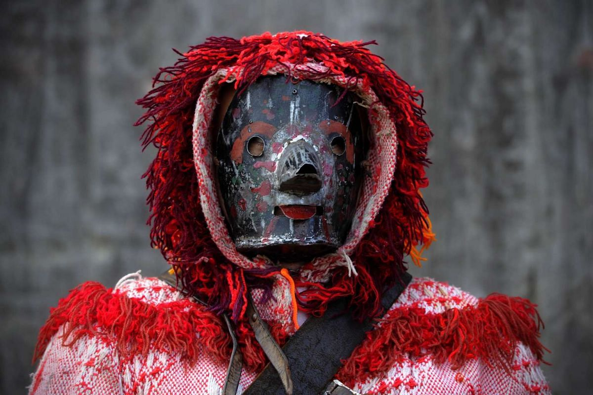 """A local dressed up in the traditional """"caretos"""" costume posing during a winter mascarade in the northern Portuguese parish of Parada de Grijo during the Sao Estebao festivities on Dec 27, 2015."""