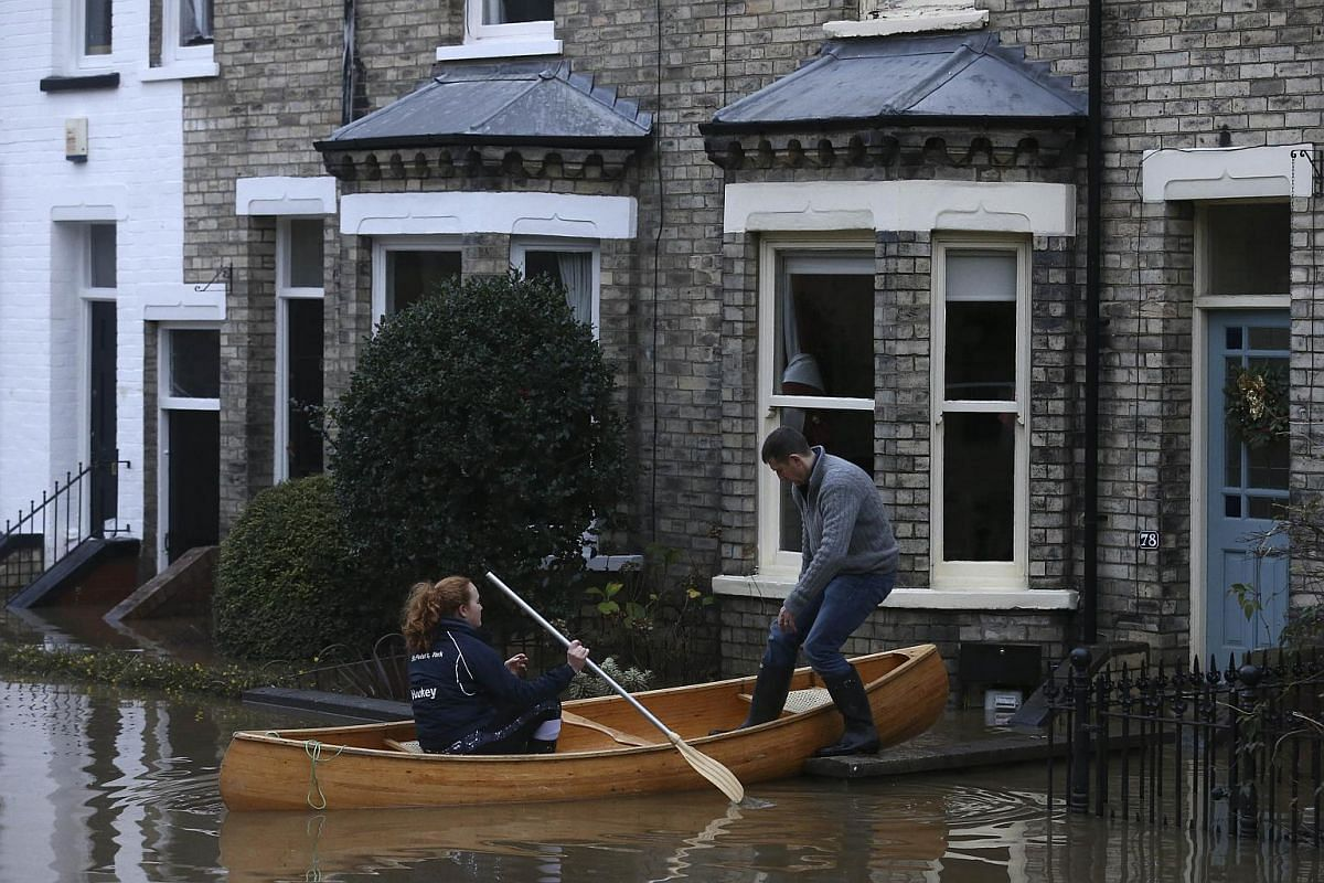 FLOODS IN ENGLAND:  Residents use a canoe to paddle to a property through floodwaters from the rivers Foss and Ouse, after they burst their banks in York, northern England on Dec 28, 2015.
