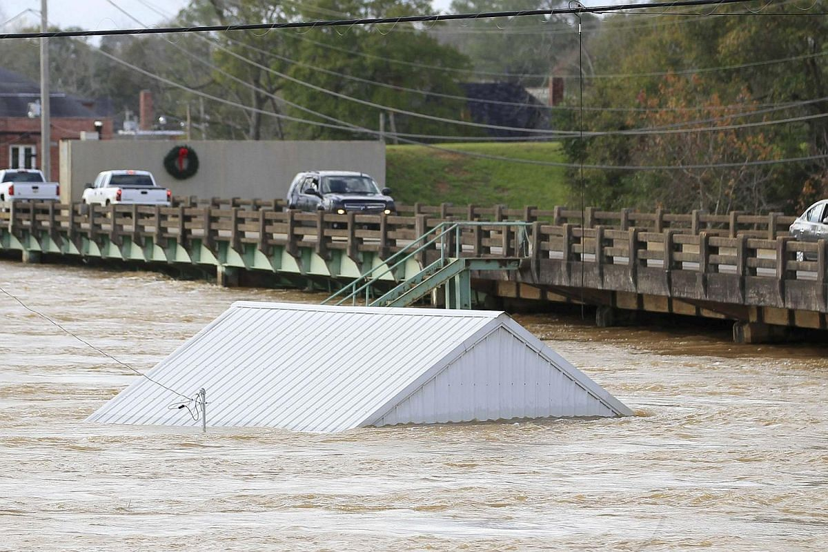 STORM IN US: The rooftop of a house is seen submerged in the Pea River in Elba, Alabama.