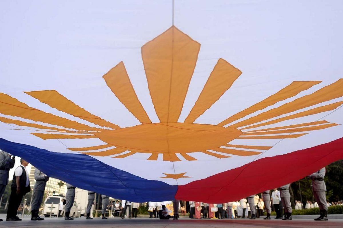 Honour guards holding the Philippine flag during the 119th death anniversary of national hero Jose Rizal at the Luneta Park in Manila, the Philippines, on Dec 30, 2015.
