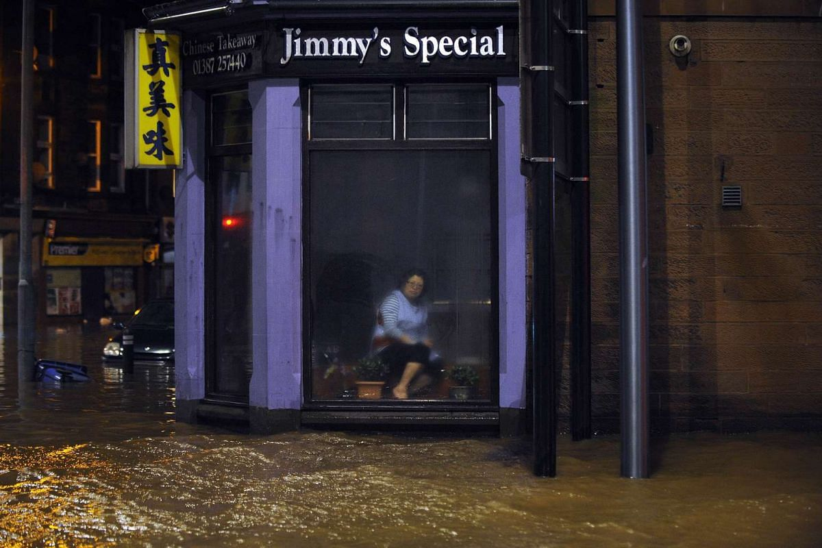 A woman sitting inside a Chinese restaurant watching floodwater race by the window in Dumfries, southern Scotland, on Dec 30, after heavy rainfall brought by Storm Frank.