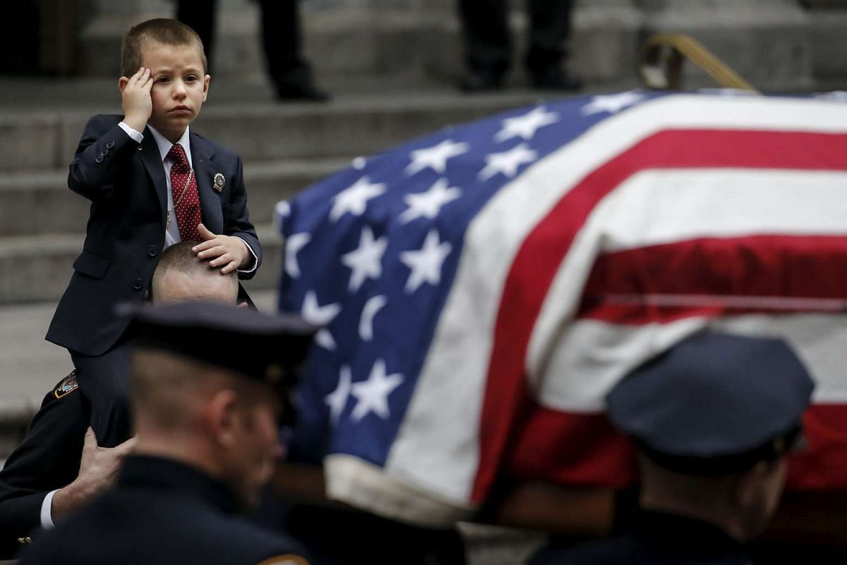 Ryan Lemm, 4, saluting as he is carried by New York Police Department officer John McCrossen as he watches the casket of his father, NYPD officer Joseph Lemm, who was killed on duty in Afghanistan, after a funeral service in New York on Dec 30.