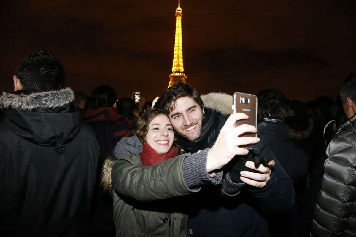 Two people take a selfie as they celebrate near the Eiffel tower during New Year celebrations in Paris on Jan 1, 2016.