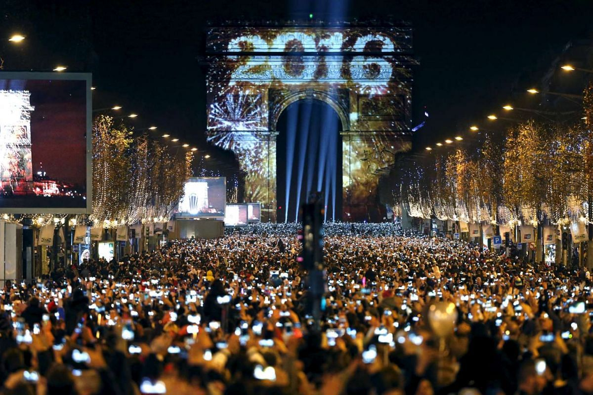 Revellers gather near the Arc de Triomphe on the Champs Elysees Avenue in Paris, France, during New Year celebrations on Jan 1, 2016.