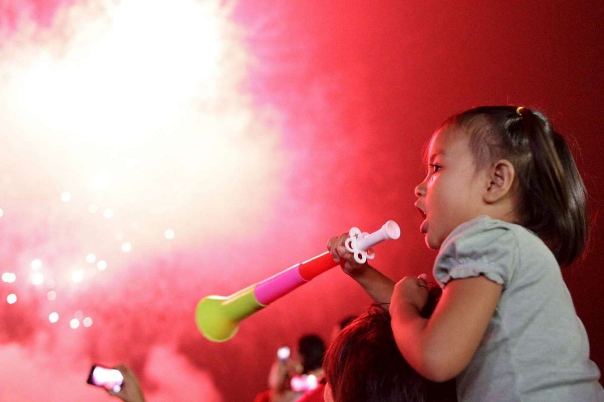A girl blows a party horn at midnight during New Year celebrations in Manila.