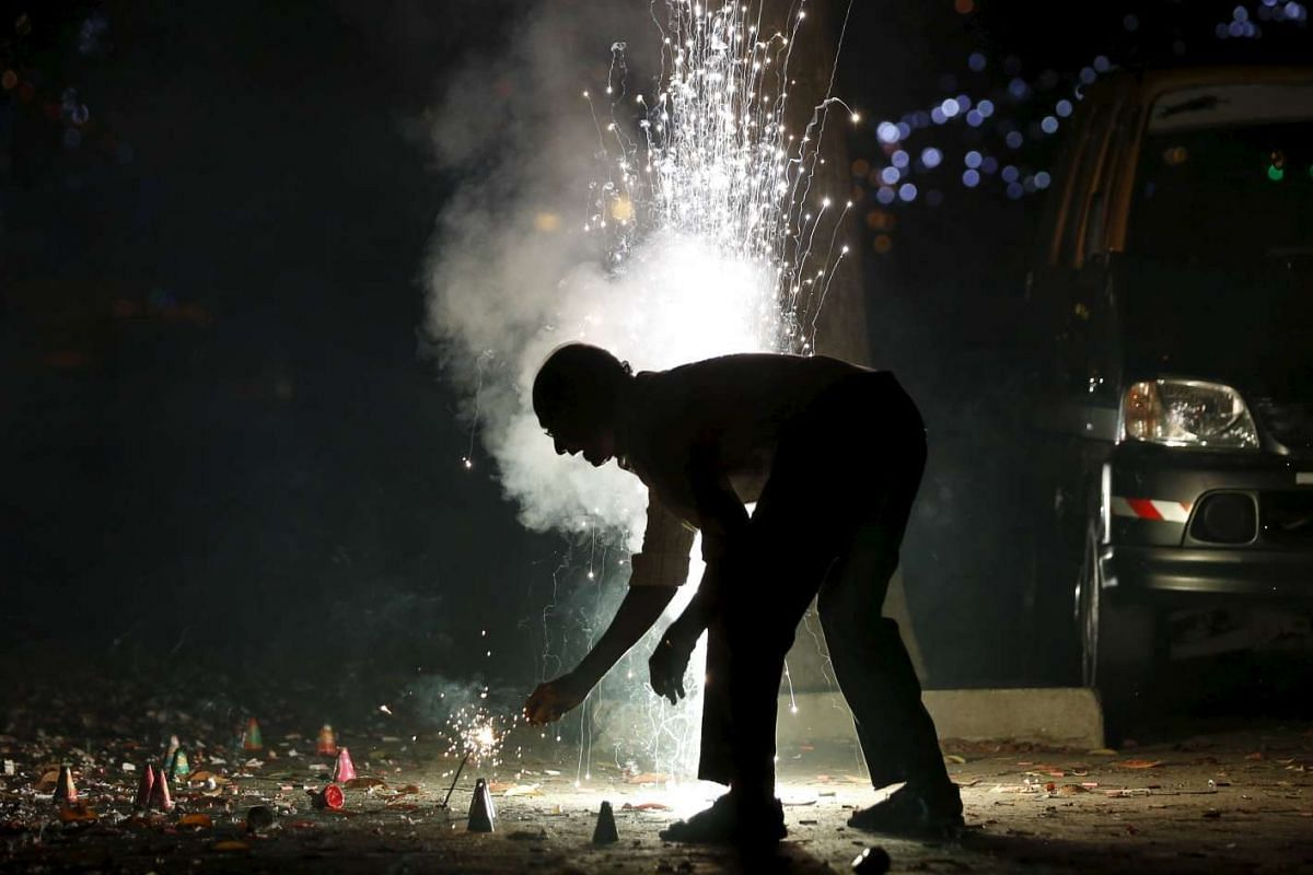 A man lights firecrackers on the street during the New Year celebrations in Mumbai, India.