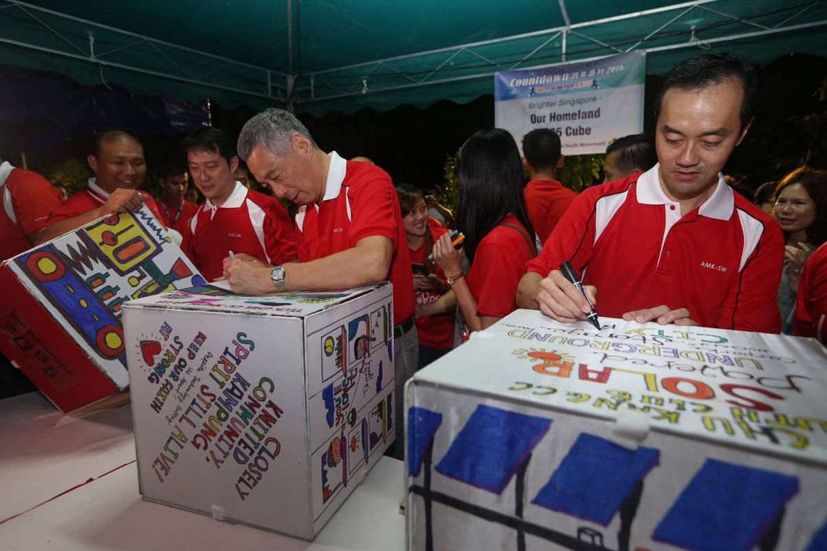 PM Lee and (right) Dr Koh Poh Koon pen down their New Year wishes on Our Homeland 2065 cubes made by youths.