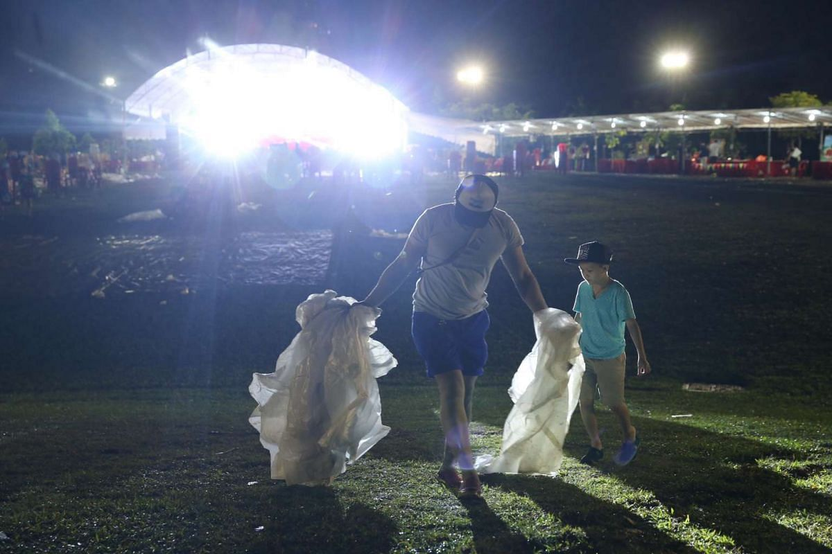 A family picks up rubbish after the countdown party.
