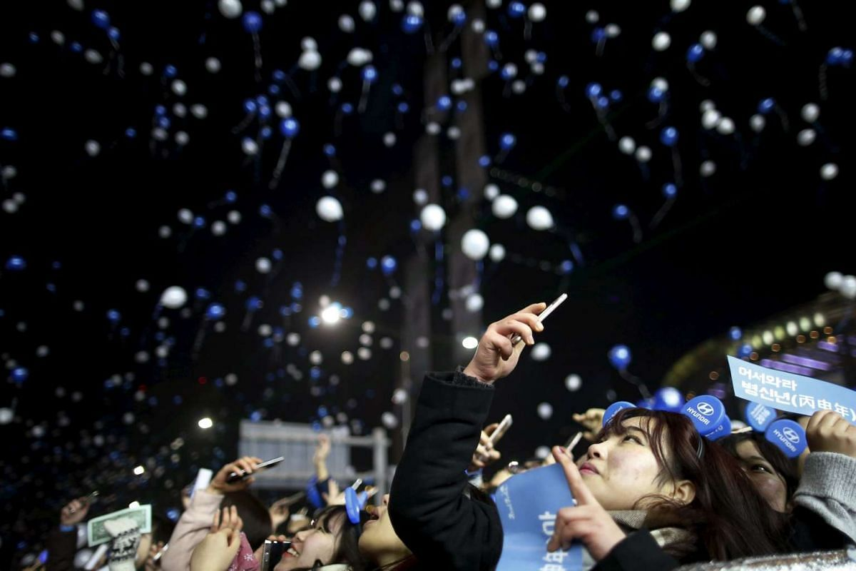 A woman takes photographs of balloons released by people gathering to celebrate the new year in Seoul.
