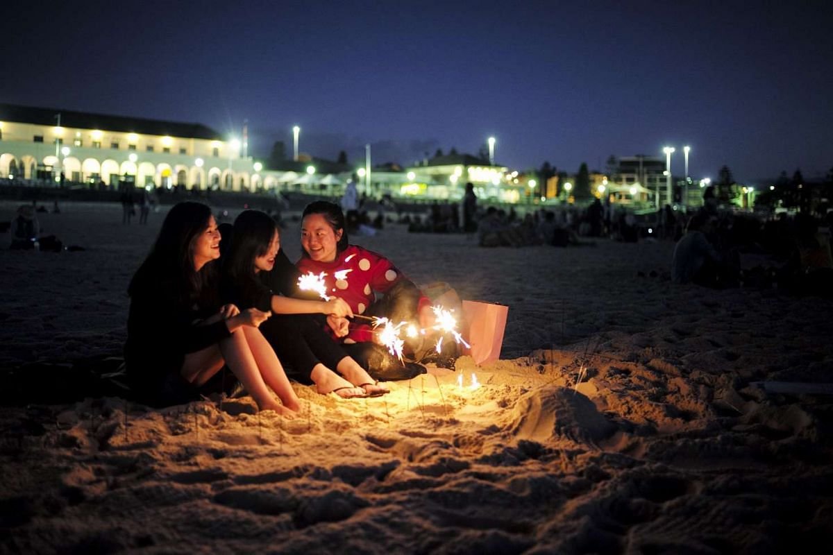 Visitors to Australia's Bondi Beach are lit by sparklers as they await the first sunrise of the new year.