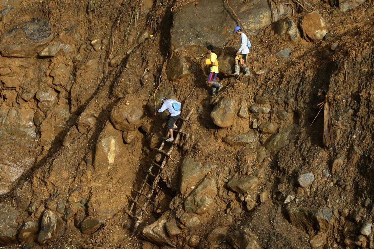Filipinos making their way across a landslide area in the mountains of Sierra Madre in the Philippines on Jan 2, 2016.