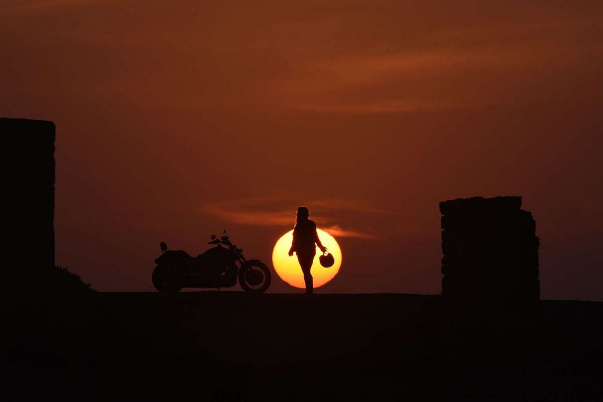 Moroccan therapist Mai Zniber posing at sunset next to her Harley Davidson motorbike on Dec 24, 2015, in the Moroccan capital of Rabat.