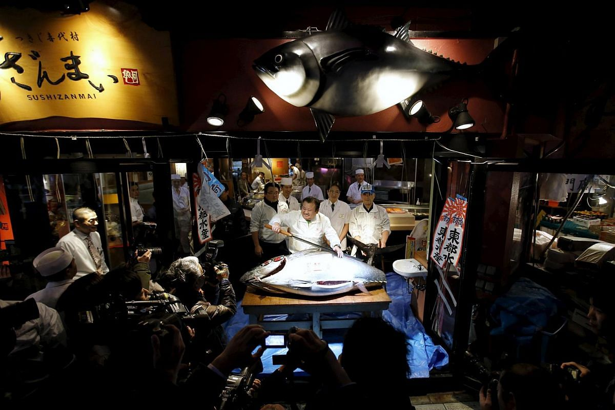 Mr Kiyoshi Kimura (centre), who runs a chain of sushi restaurants, holding a sword as he poses with a 200kg bluefin tuna at his restaurant outside the Tsukiji fish market in Tokyo.