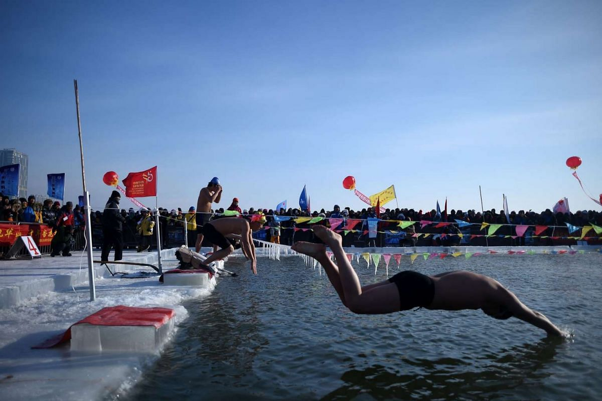 Swimmers jumping into a pool carved from thick ice during an ice swimming competition at the Harbin International Ice and Snow Festival in China on Jan 5, 2016.