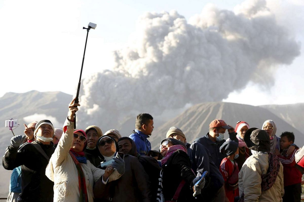 Tourists taking a group photo as Mount Bromo erupts near Ngadisari, East Java, Indonesia, on Jan 6, 2016.