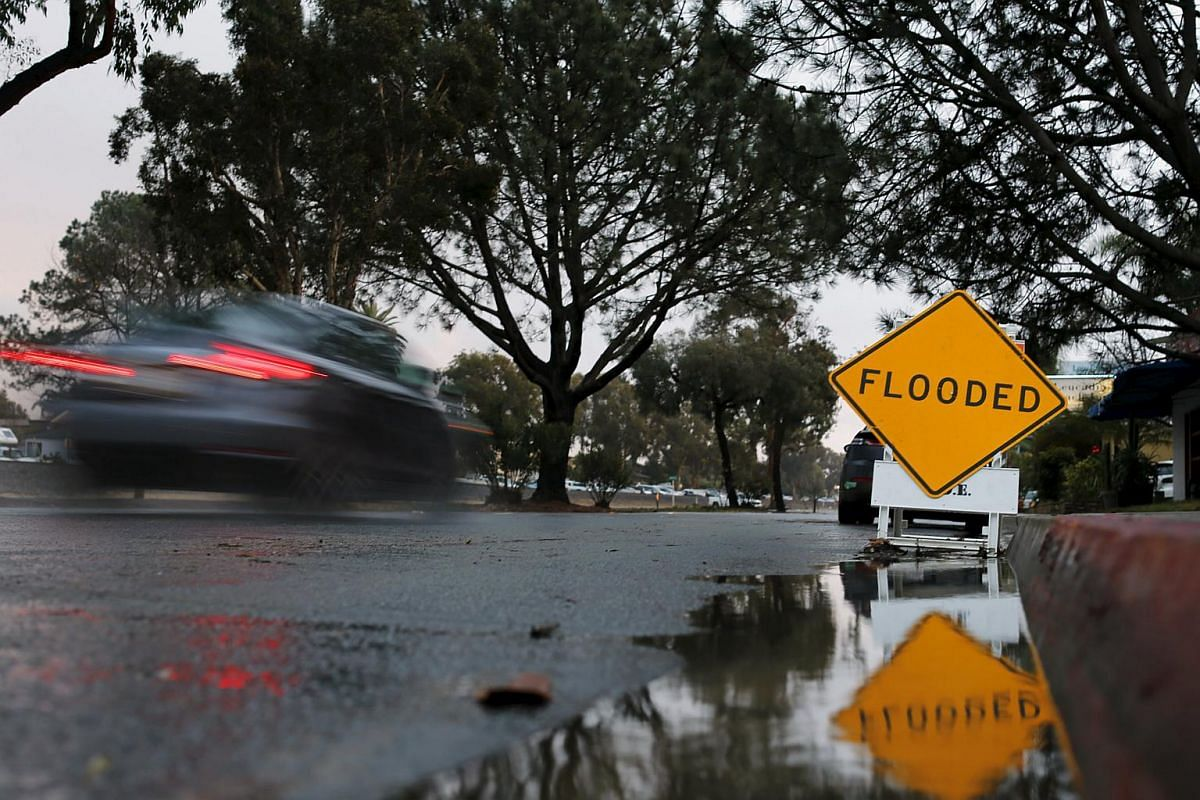 A car passing a sign warning of flooding following a storm in Leucadia, California, on Jan 5.