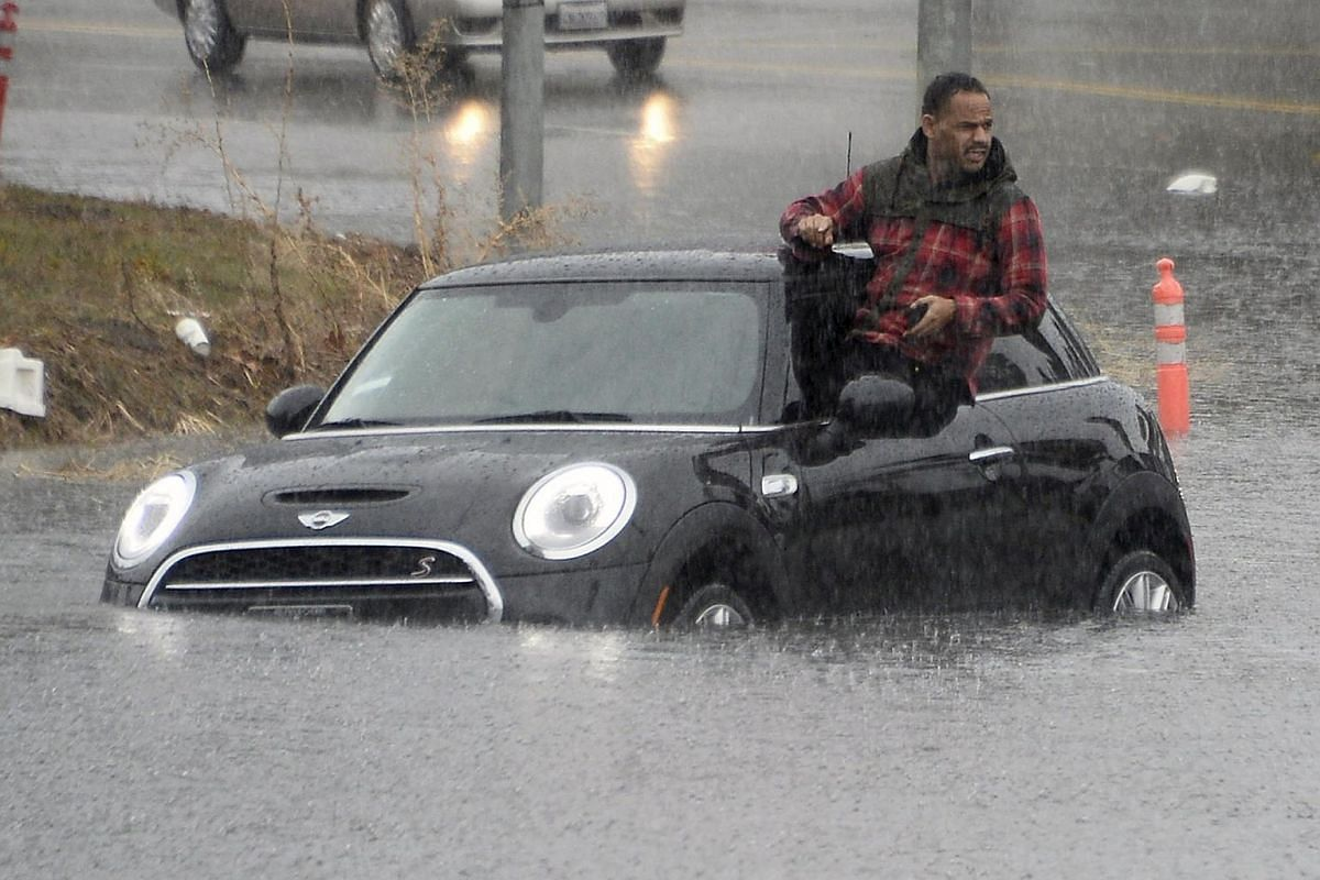 A driver climbing out of a window of his car after driving onto a flooded road in Van Nuys, California, on Jan 5.