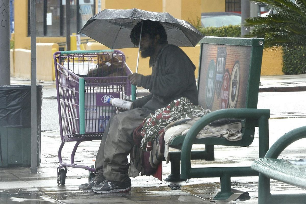 A homeless man waiting at a bus stop during a storm in Los Angeles, California, on Jan 5.