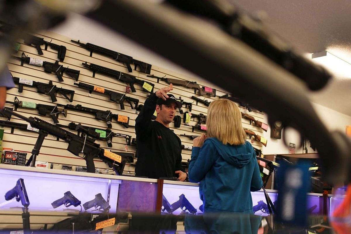 A customer picking up handguns at a store in Florida on Jan 5, 2016, the day that US President Barack Obama announced his executive action on guns.