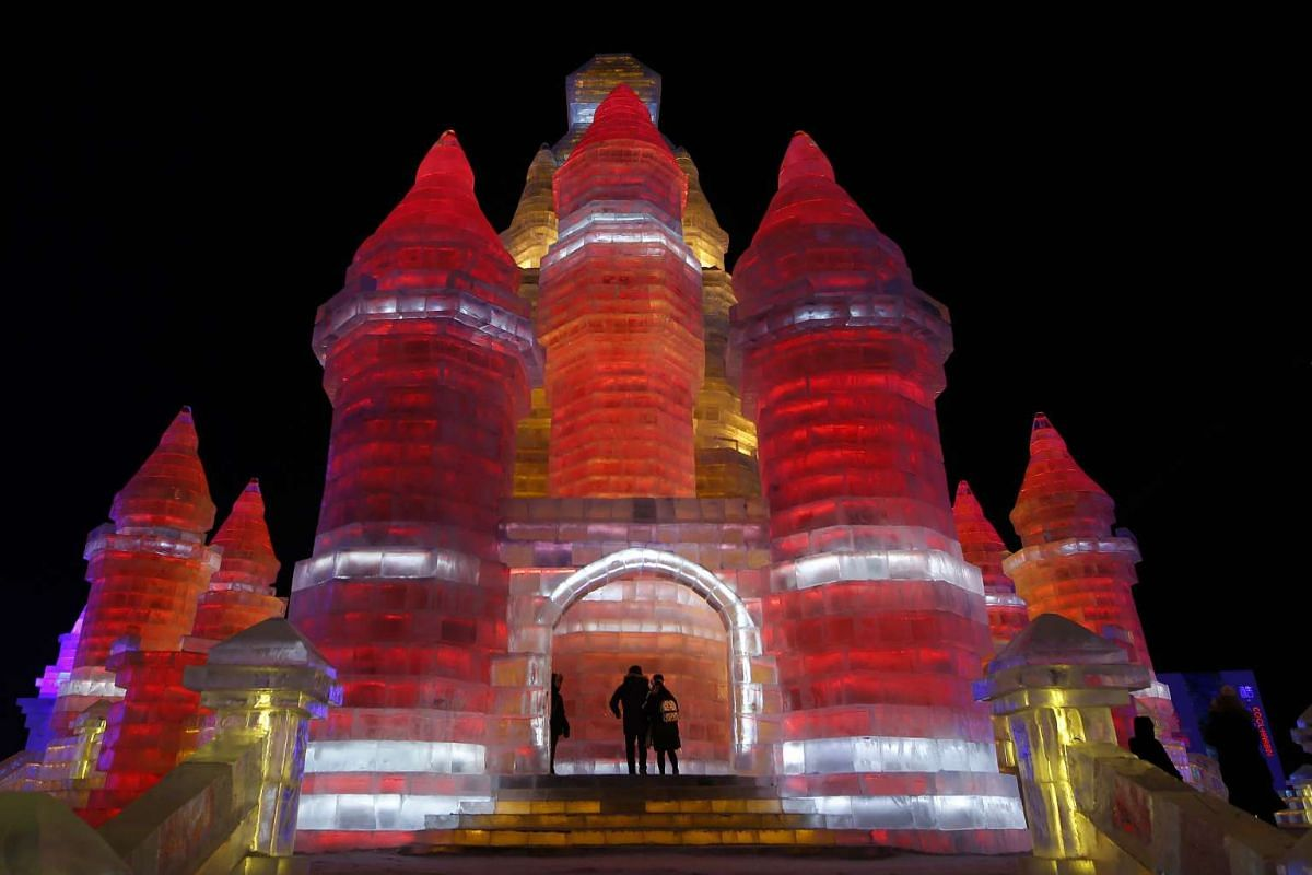 An ice building bathed in yellow and red lights on the opening day of the Harbin International Ice and Snow Festival on Jan 5, 2016.