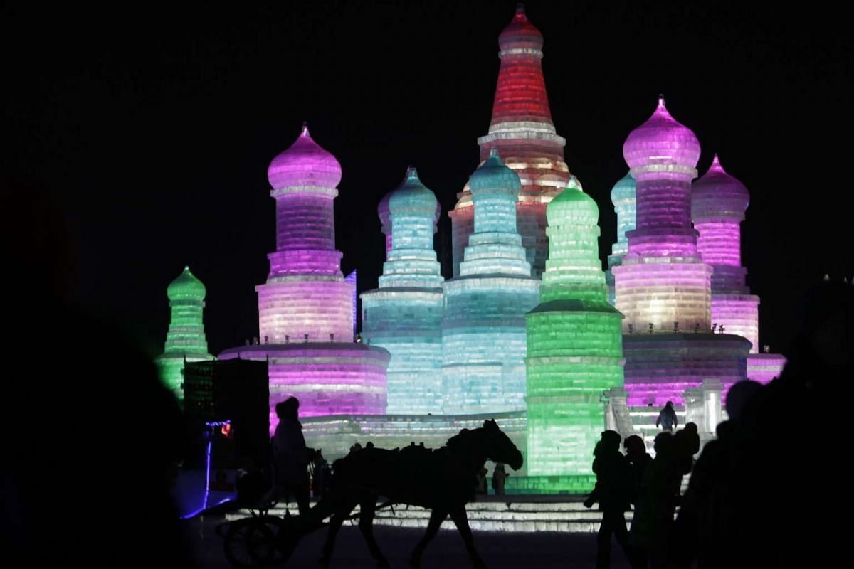 Visitors viewing ice sculptures illuminated by coloured lights on the opening day of the Harbin International Ice and Snow Festival on Jan 5, 2016.