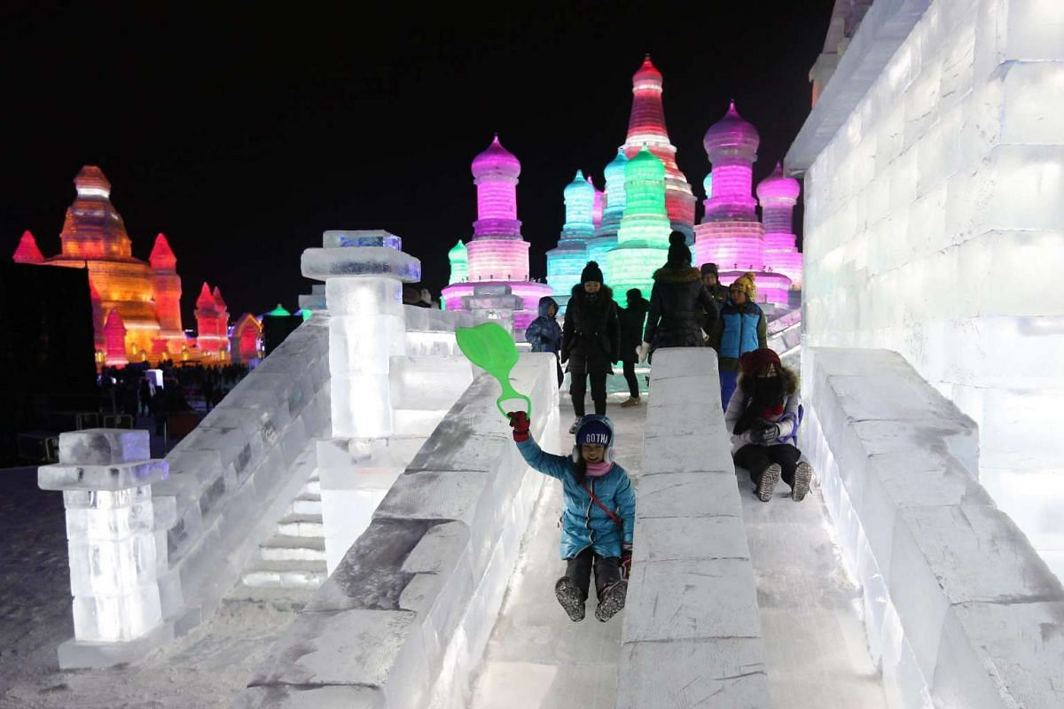 Visitors riding on ice slides of large ice sculptures during the opening ceremony of the 32nd Harbin International Ice and Snow Festival on Jan 5, 2016.