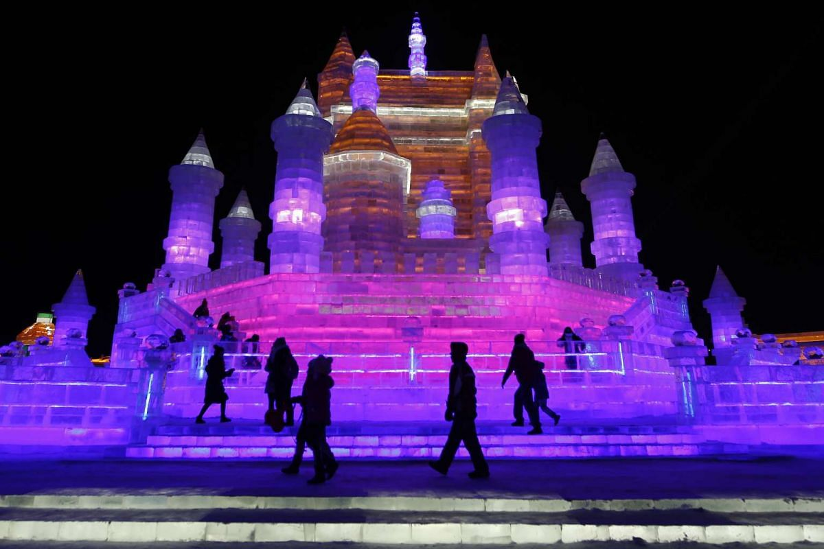 Visitors treading on ice sculptures illuminated by coloured lights on the opening day of the Harbin International Ice and Snow Festival on Jan 5, 2016.