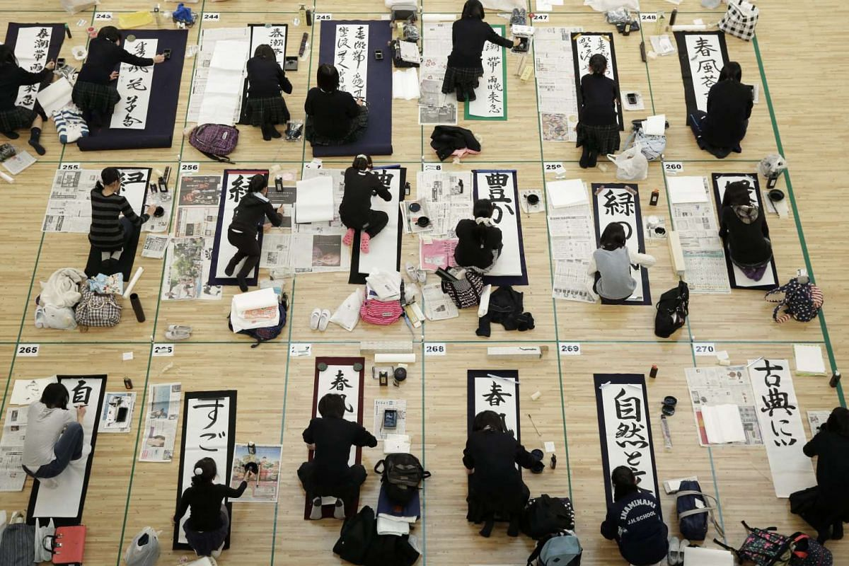 Participants writing on papers with ink brushes in the New Year calligraphy contest at the Nippon Budokan Hall in Tokyo on Jan 5, 2016.