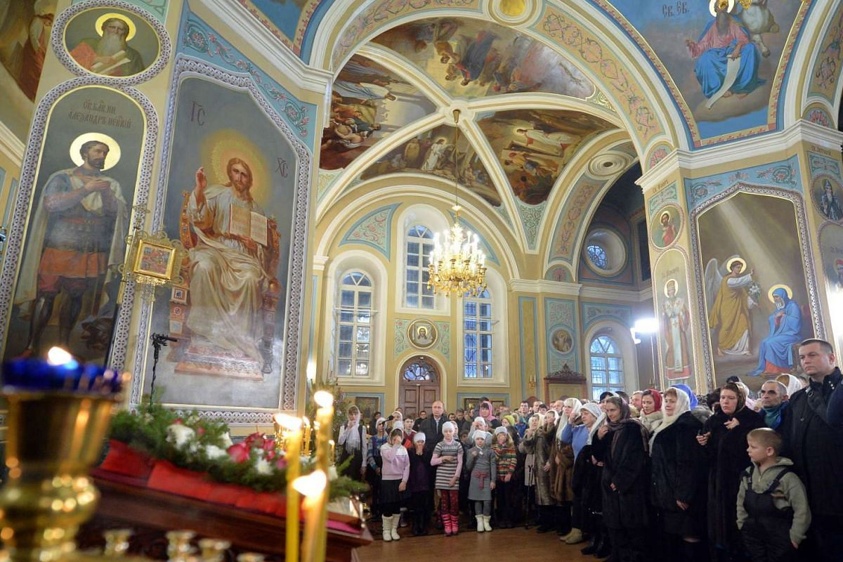 Russian President Vladimir Putin (centre) attending a Christmas service in the Church of the Intercession in the village of Turginovo on Jan 6, 2016.