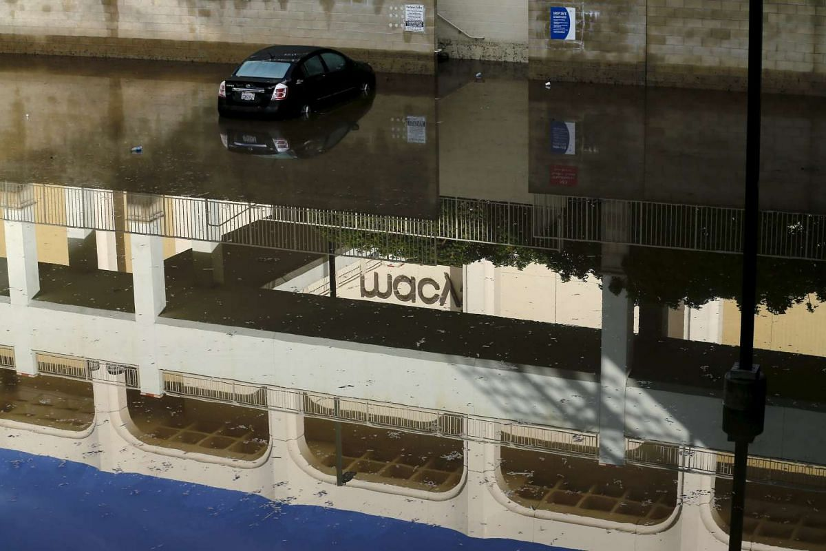An abandoned car in floodwaters at a shopping mall after a storm in San Diego, California, on Jan 6, 2016.