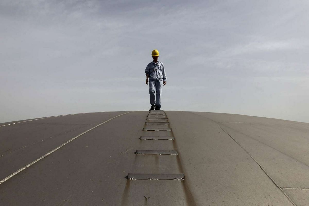 An employee walking on top of an oil tank at a Sinopec refinery in Wuhan, Hubei province, in 2012. China is building underground caverns capable of holding up to a quarter of its expanded strategic oil reserves by 2020.