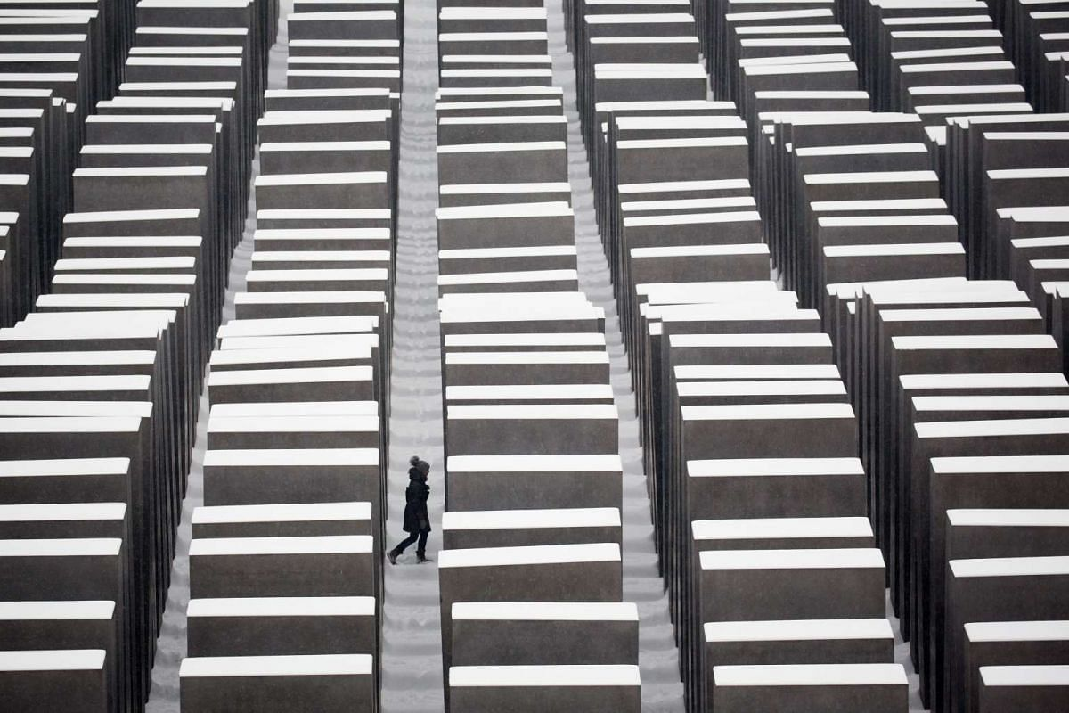 A visitor walking through the snow covered Holocaust memorial in Berlin, Germany, on Jan 6, 2016.