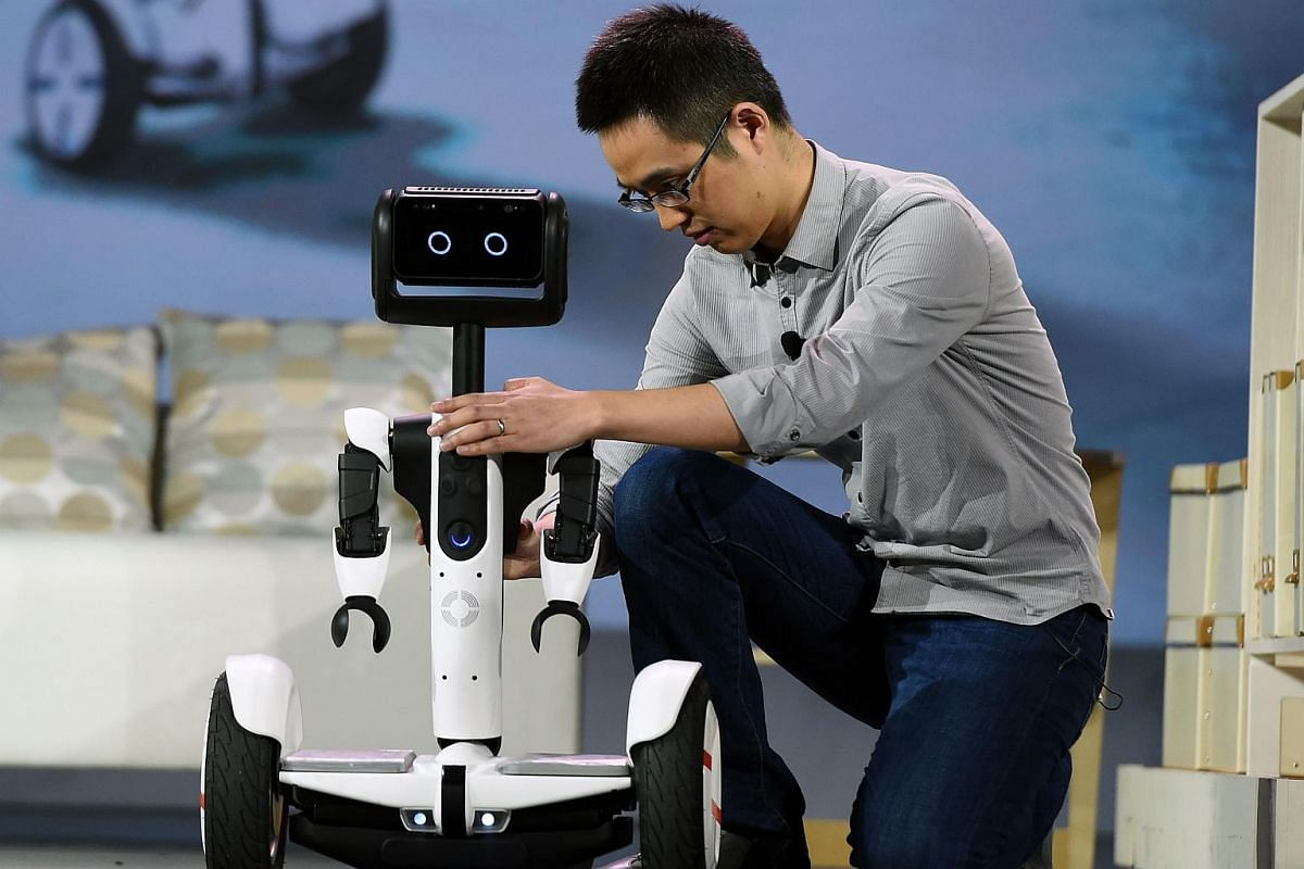 Arms are affixed to a self-balancing Ninebot Segway personal transportation robot during a keynote address by Intel Corp.