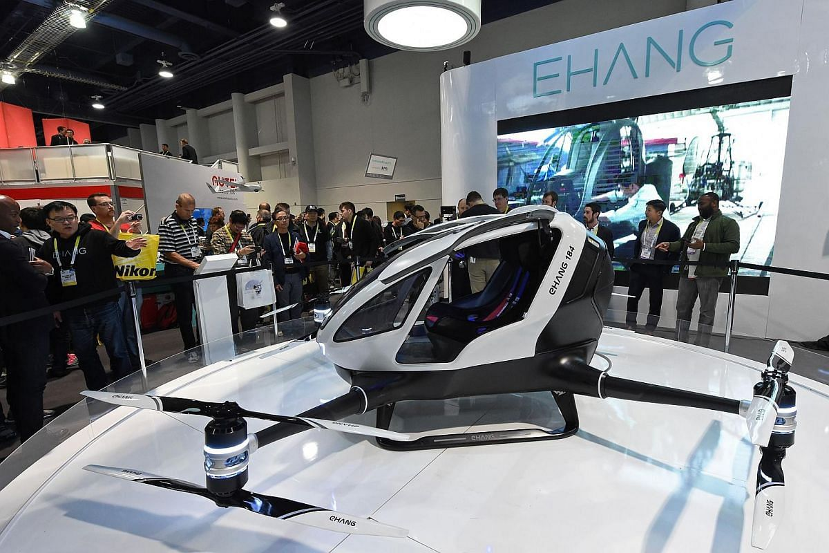 Attendees looking at an EHang 184 autonomous-flight drone that can fly a person, at CES 2016.