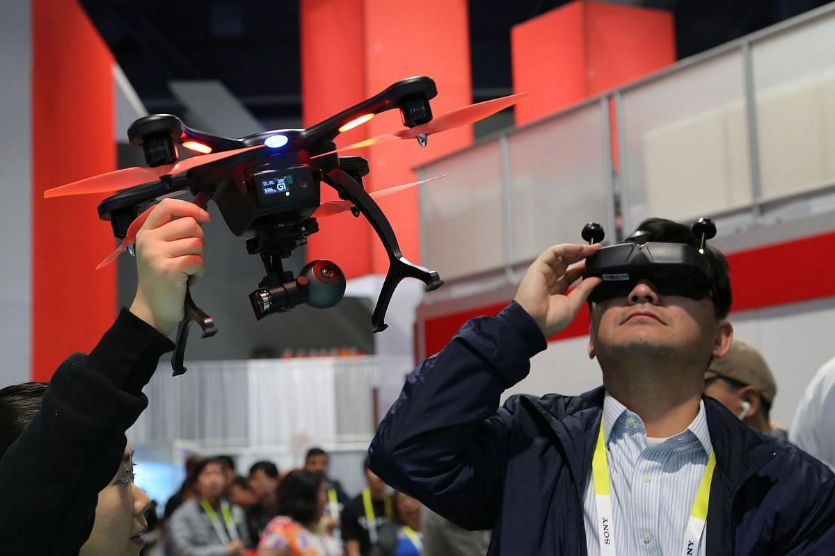A man trying out virtual reality goggles with an EHang Ghost Drone 2.0, which has 4K video, Avatar tilt control and VR goggles at CES 2016.